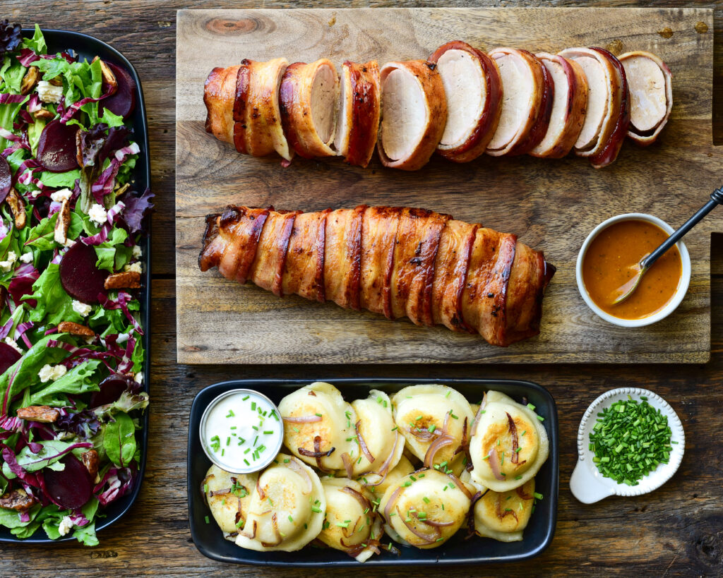 Two bacon wrapped pork tenderloins. (One is sliced showing the juicy interior) A dish of pierogis and salad are also part of the meal.