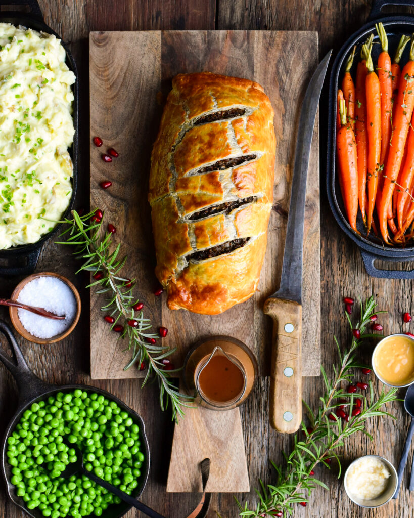 Top down image of a Beef Wellington on a cutting board with a large carving knife and sauce. Carrots, peas and mashed potatoes surround the beef.