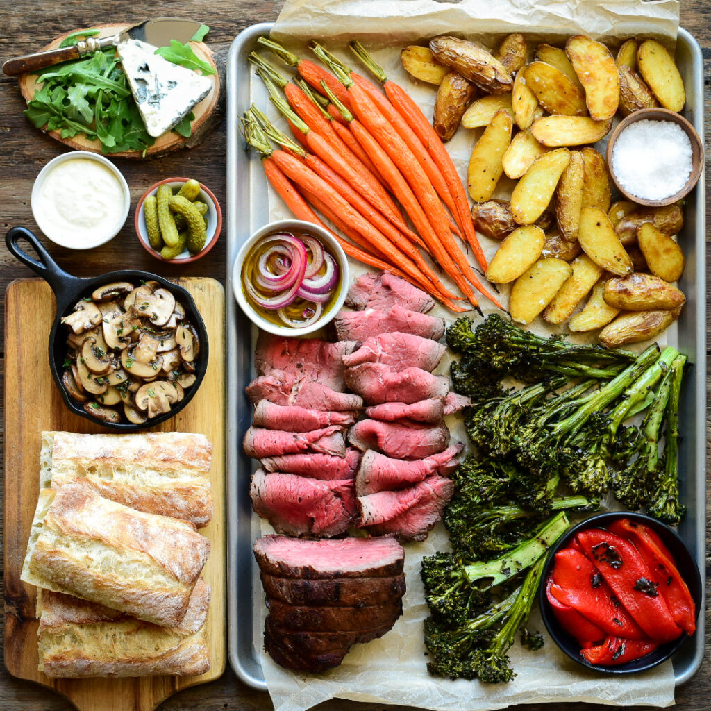 Roast beef dinner platter with carrots, potatoes, brocolini, roasted red pepers and sandwich fixings.