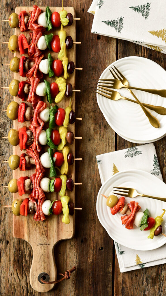 A top down image of a narrow wooden cutting board with antipasto skewers all lined up in a row.