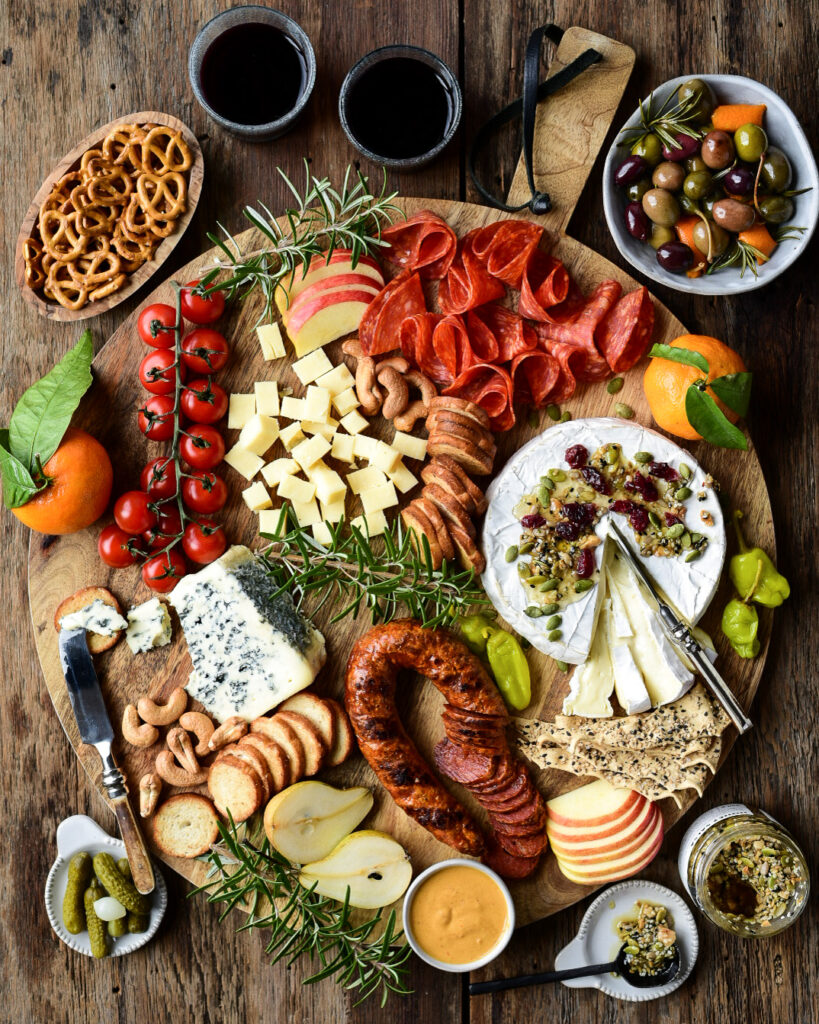 A round charcutterie board with meats, cheeses, fruit and a bowl of warmed olives.