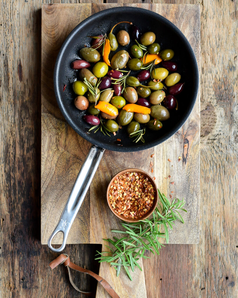 A small black skillet with olives, rosemary and citrus peels.