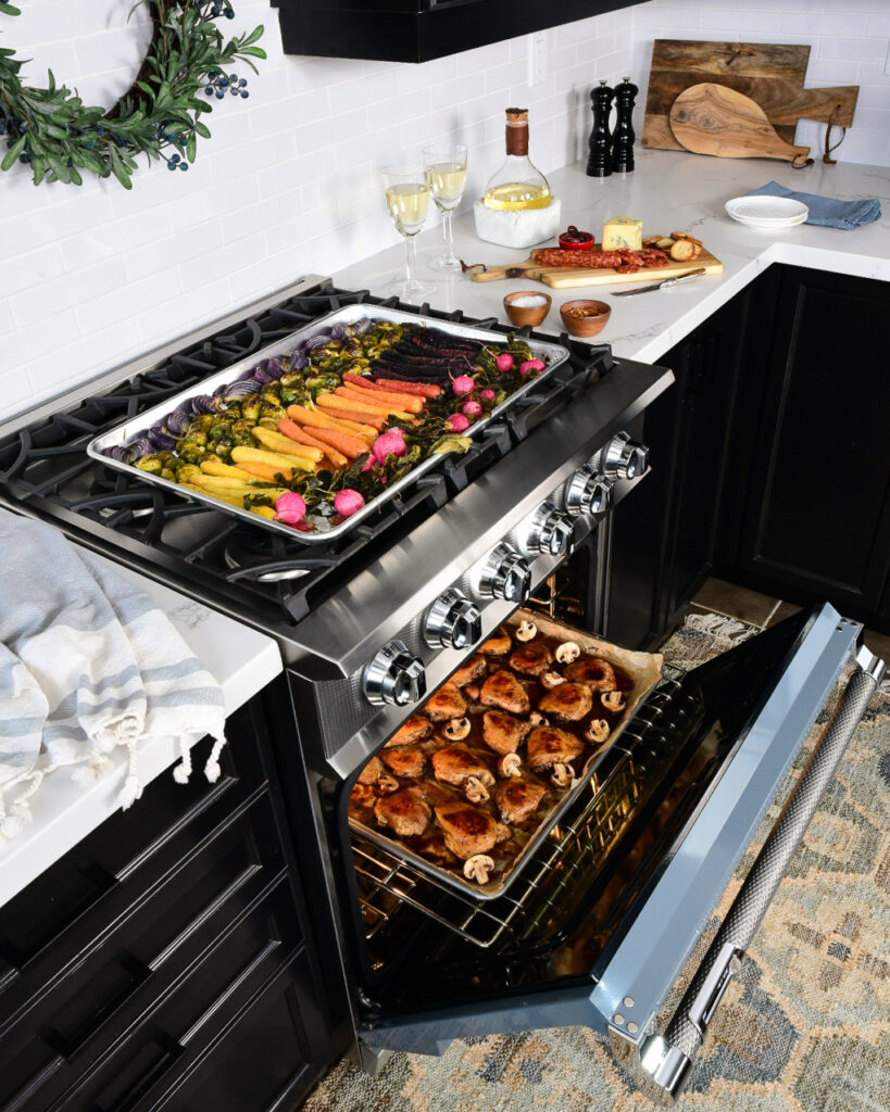 An image taken in a kitchen with the range open with a sheet pan of roasted chicken inside and a tray of colourful roasted vegetables on the top.