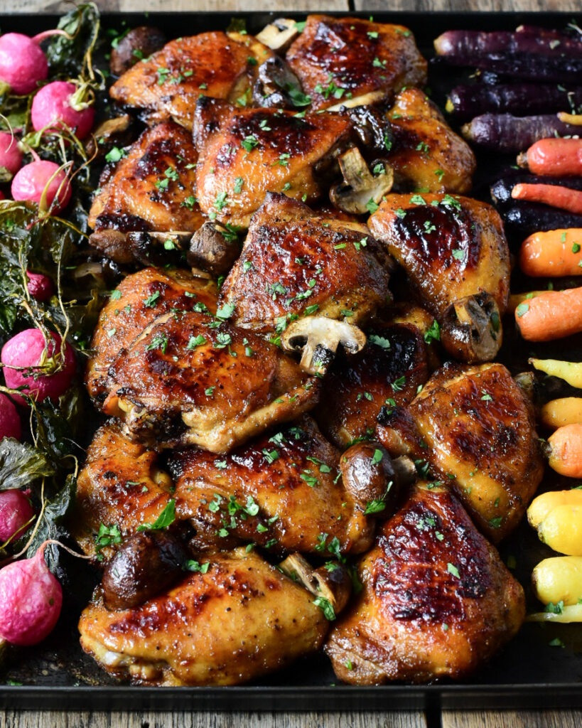 At top down image of glazed and roasted Chicken Thighs with mushrooms and vegetables on the side.