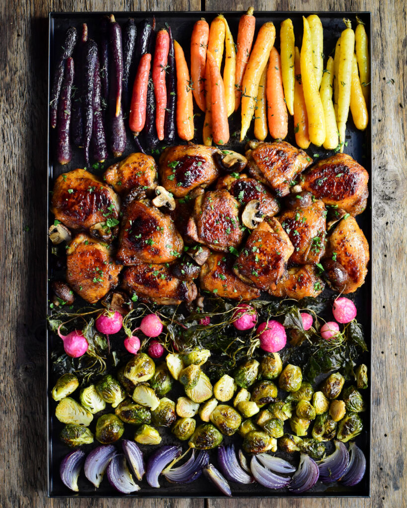 A very colourful sheet pan of roasted vegetables and glazed chicken thighs.
