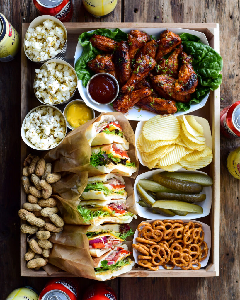 A top down image of Zimmy's Antipasto Sandwiches, Crispy and Sticky Chicken Wings (+extra sauce for dipping), pretzels & mustard, chips, pickle spears, peanuts, Smoked Parmesan Herb Popcorn, and a few beverages in a wooden tray ready for delivery.