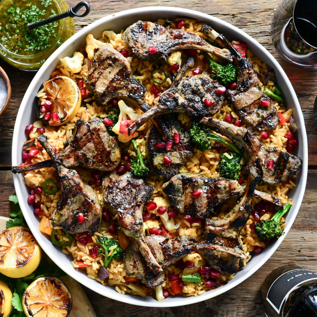 A top down image of a round platter of grilled lamb lollipops served over mixed vegetable rice and pomegranate arils.