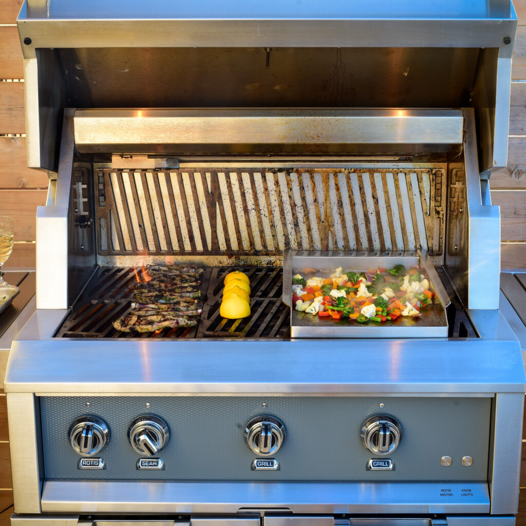 An open grill with lamp chops, lemons and vegetable being cooked.