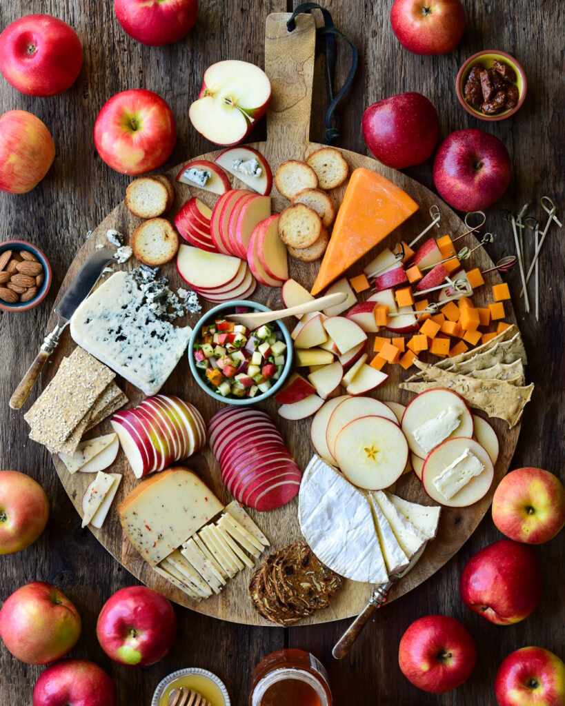 A large round board filled with cheese and apple pairings. This board is surrounded by a beautiful variety of apples.