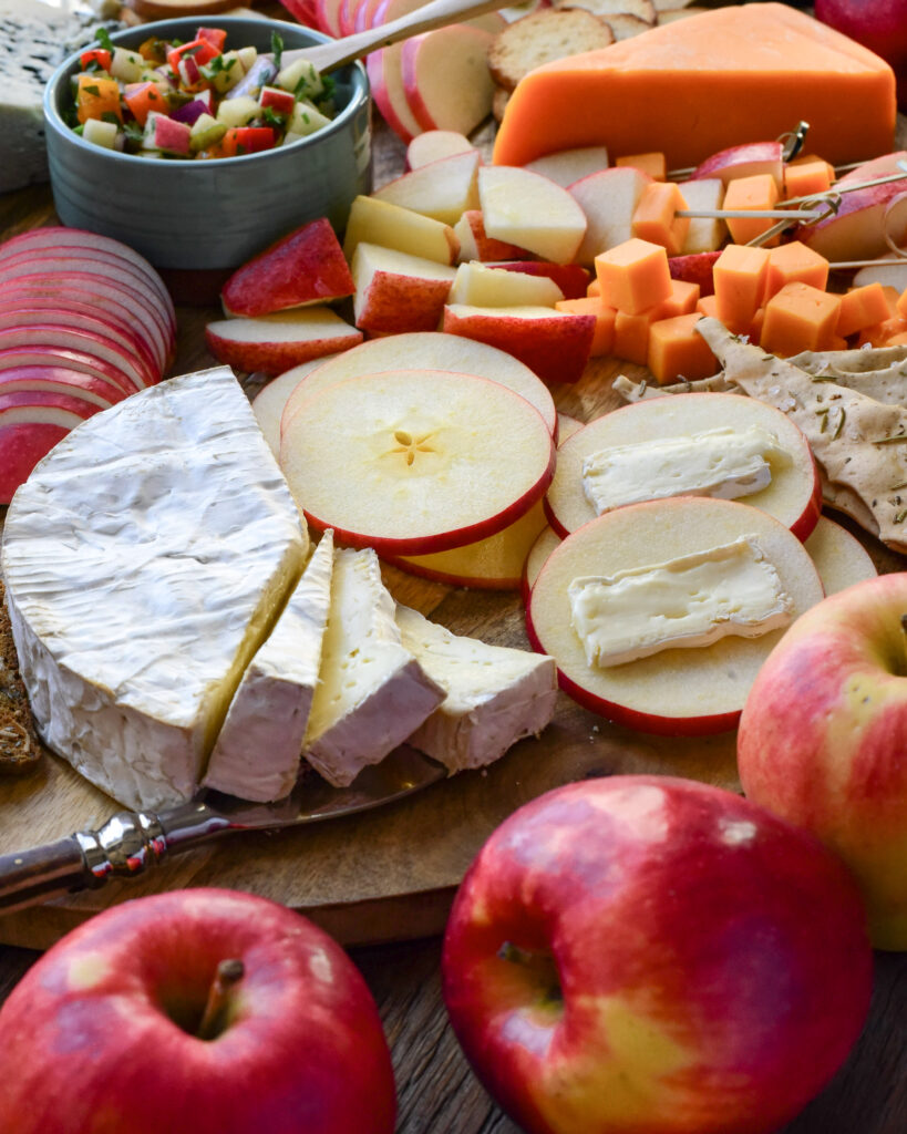 A close up image of an apple and cheese board, featuring slices of brie and apple circles.