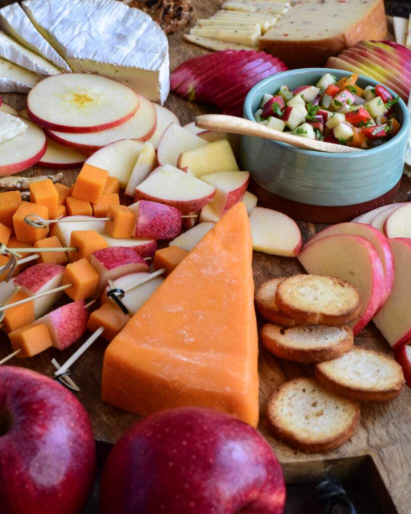 A close up image of an apple and cheese board, featuring a wedge of cheddar cheese and skewers of cheese and apples.
