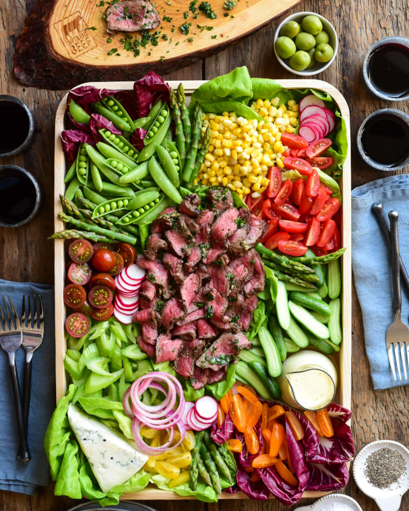 A bright and colourful grilled beef salad. Ribbons of medium rare beef are place in the middle of the tray and is surrounded by stack/piles of fresh vegetables, salad dressing and blue cheese.