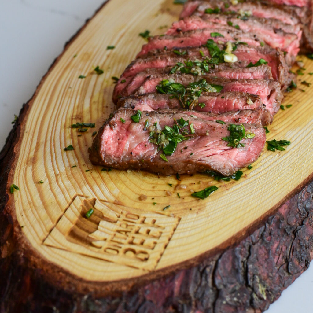 Medium rare slices of Ontario beef on a wood (bark still on the edges) board. The beef is resting in a board sauce and will be added to this grilled beef salad.