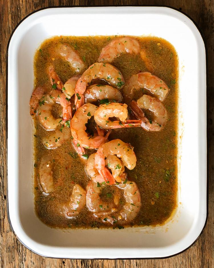 An white enamel pan with black edges filled with shrimp in a marinade for ridiculously good grilled shrimp.