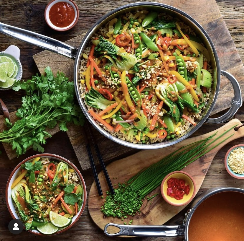 A top down image of a pan and a bowl of Red Thai curry peanut sauce and vegetables. Also layed out is cilantro, crushed peanuts, chopped chives and a pot of sauce.