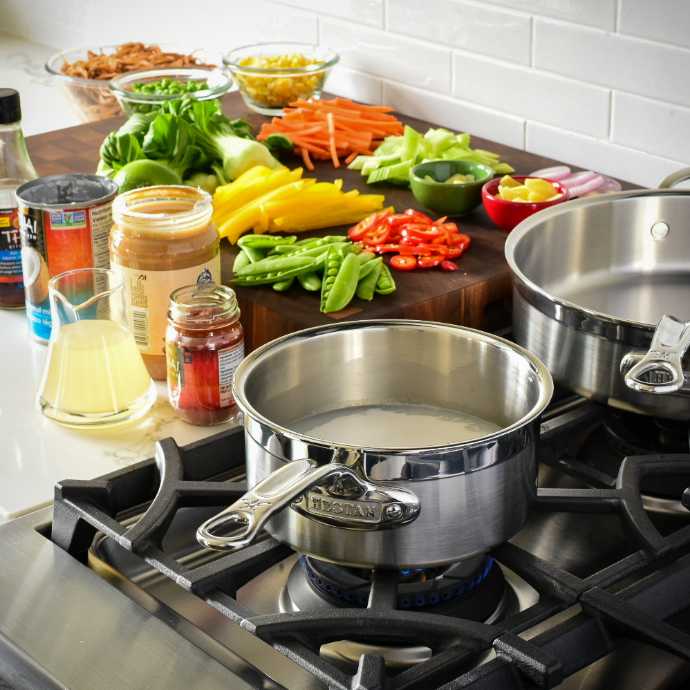 An image of two pans on the range with vegetables and other ingredients ready