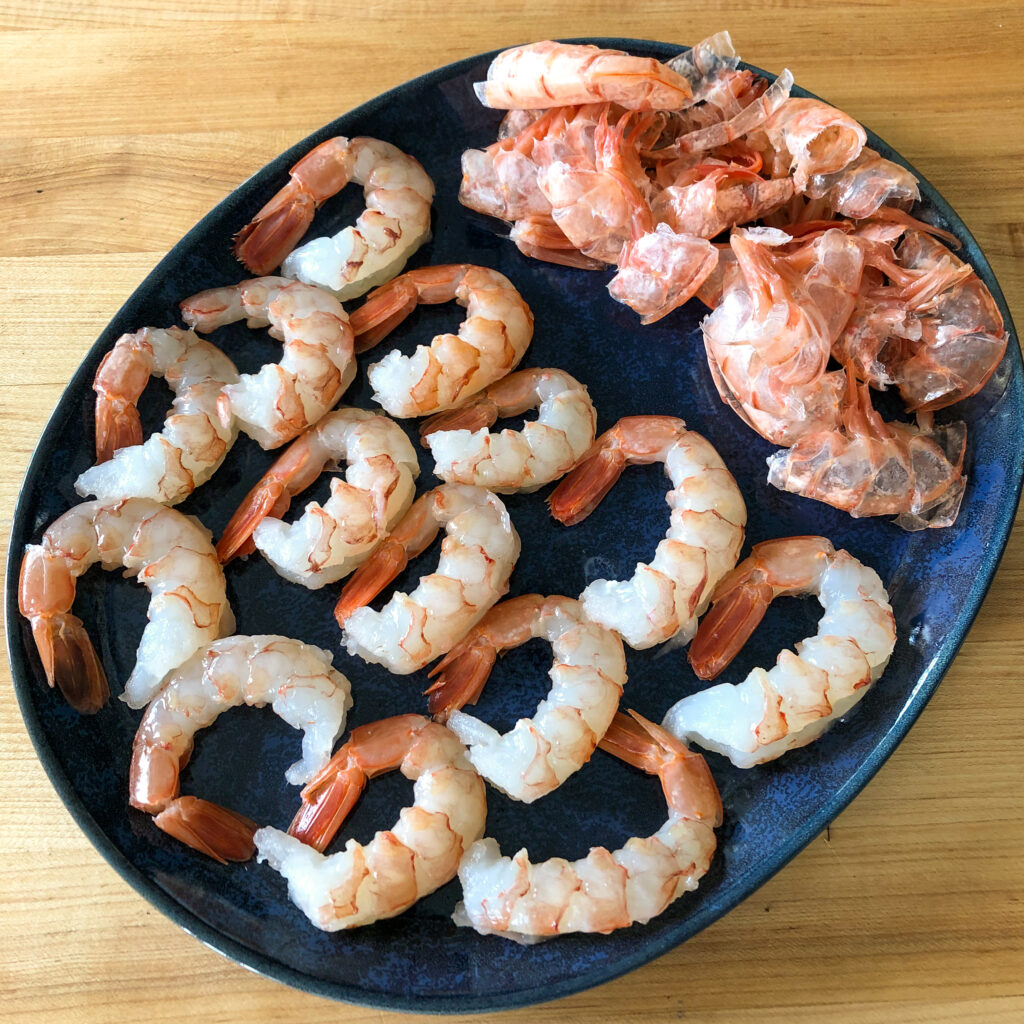 A blue oval plate of shrimp, shells removed and tails remain on.