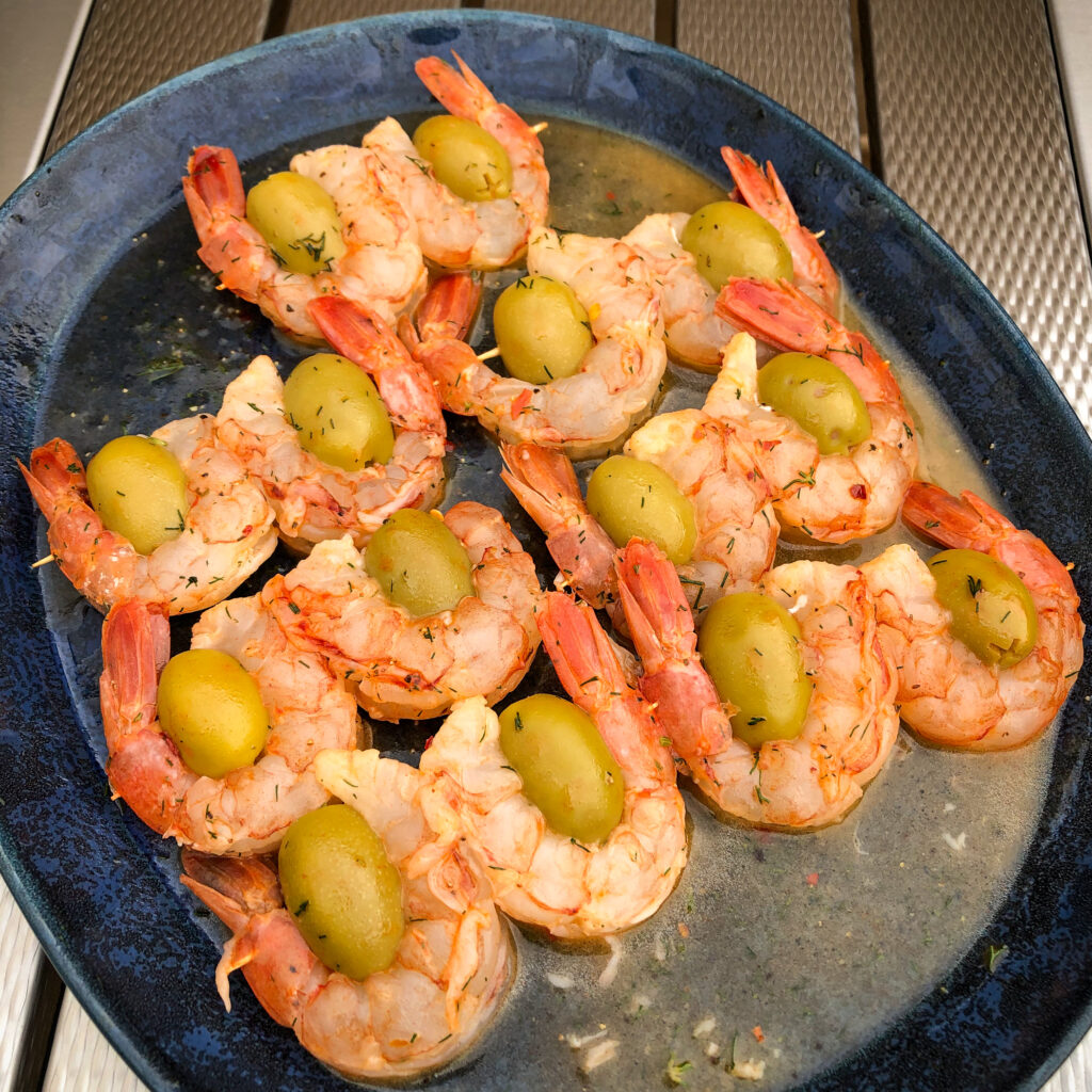 A blue oval plate with shrimp and olive skewers ready to go on the grill