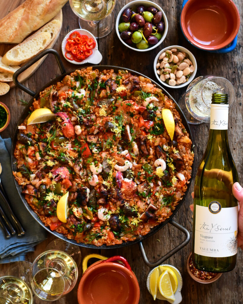 A large, colourful pan of paella filled with seafood, poultry, rice and veggies. This pan is surrounded by a bottle of Viognier, glasses of wine, nuts, olives, lemons and bowls.