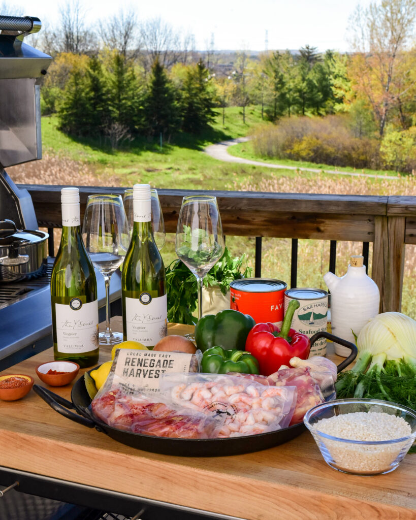 This is an image of two bottles of wine, wine glasses and ingredients for paella sitting on a table outside beside the grill with a meadow in the background.