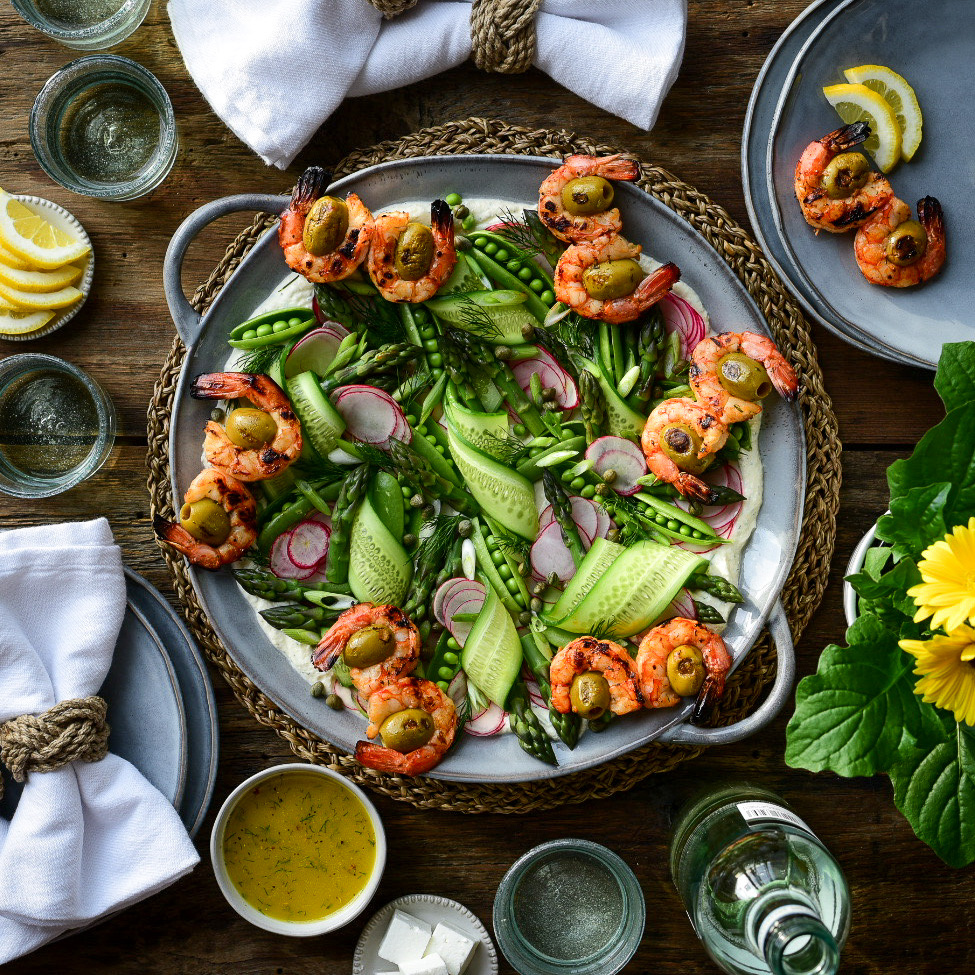 A top down image of a spring salad with grilled wild shrimp, ribbons of cucumber, snap peas, radishes, asparagus tips and green onions . Plates, napkins, wine, glasses, and sauce all surround this dish.
