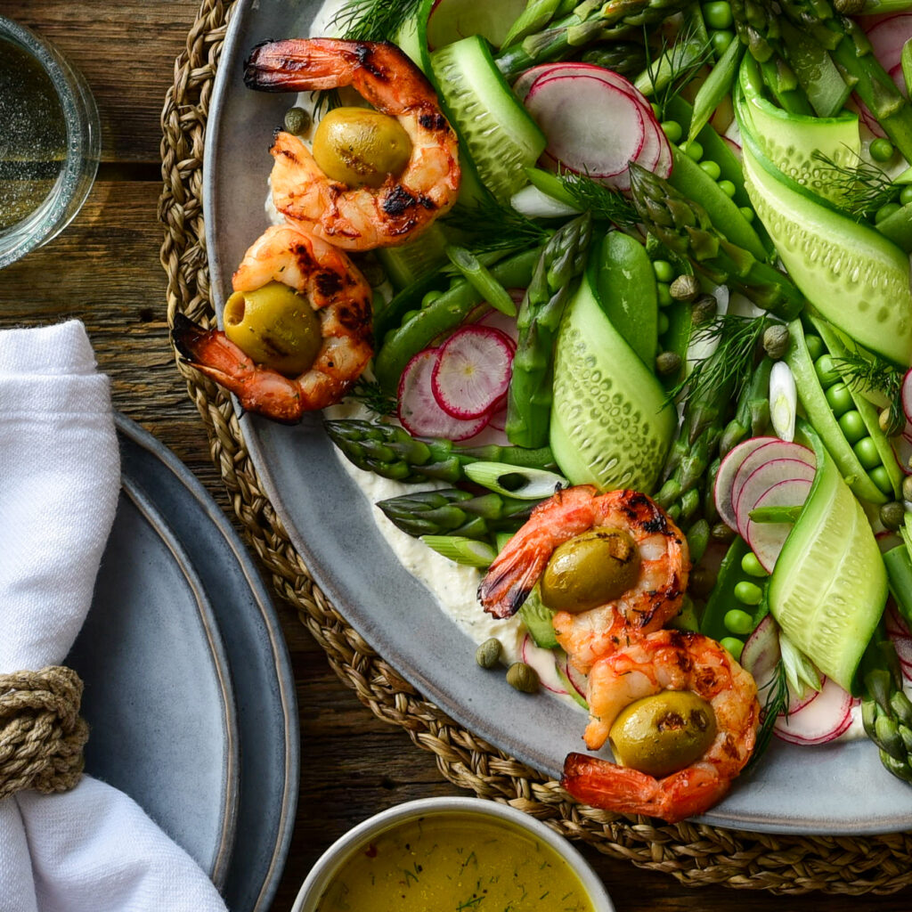 A close up of a top down image of a spring salad with grilled wild shrimp, of ribbons of cucumber, snap peas, radishes, asparagus tips and green onions.