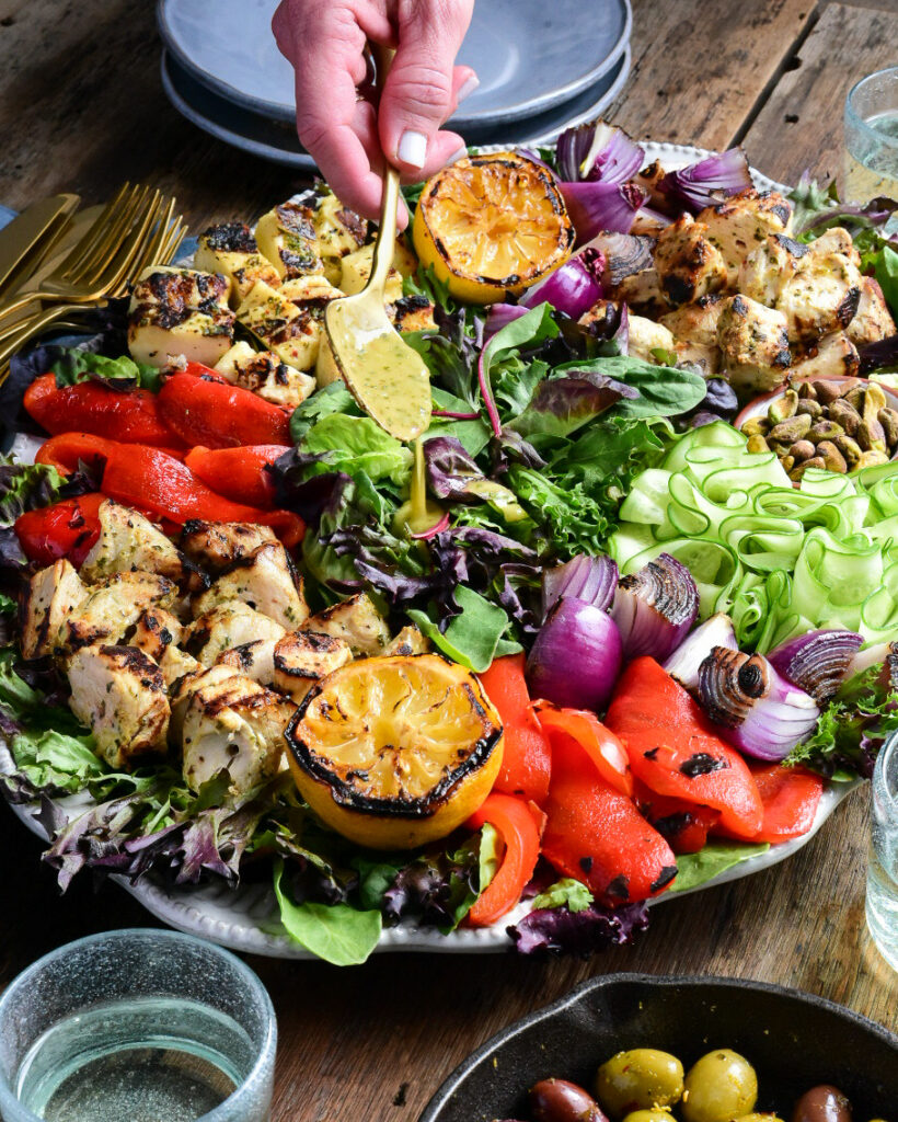 An image of a large a Grilled Mediterranean Chicken & Halloumi Herb Salad with someone spooning dressing on it. This oval platter has piles of cubes of grilled chicken, halloumi, onions, red peppers, lemons and ribbons of fresh cucumber and pistachios. A small cast iron pan with warmed olives, a bowl of dressing and dishes surround this platter.