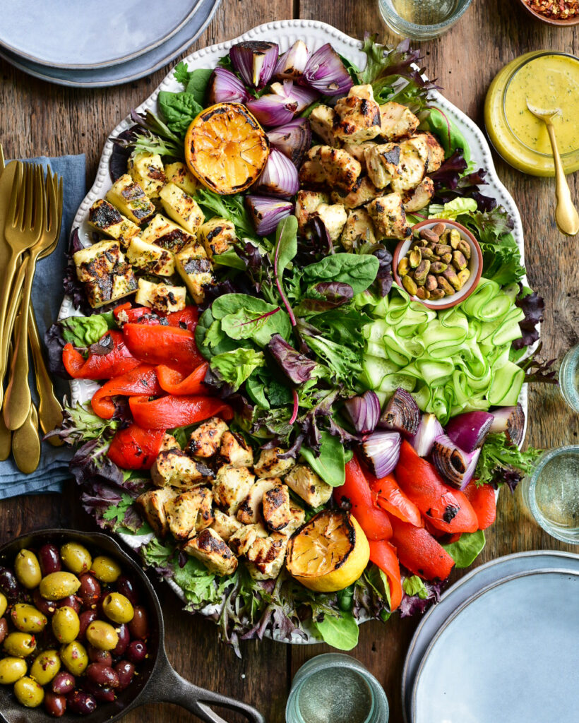 An image of a large a Grilled Mediterranean Chicken & Halloumi Herb Salad. This oval platter has piles of cubes of grilled chicken, halloumi, onions, red peppers, lemons and ribbons of fresh cucumber and pistachios. A small cast iron pan with warmed olives, a bowl of dressing and dishes surround this platter.