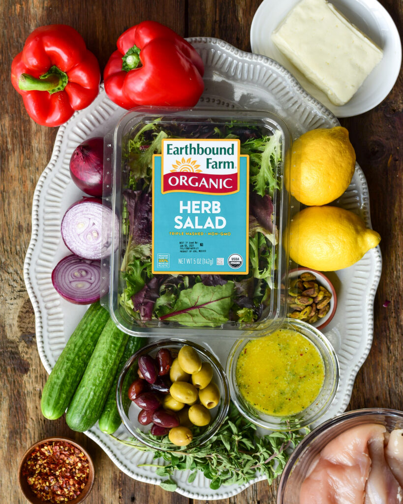 An image of a box of Earthbound Farm Organic Herb Salad surrounding other ingredients to make this grilled Mediterranean Chicken and Halloumi Herb Salad.