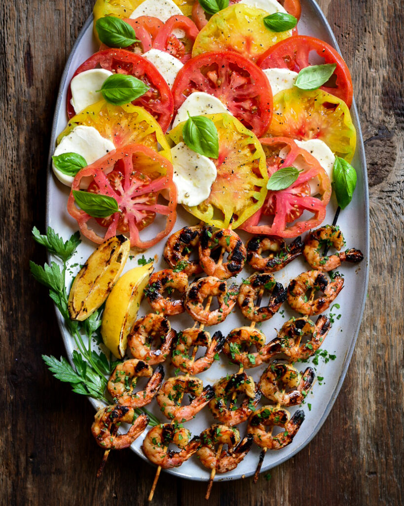 Four skewers of grilled shrimp with parsley and grilled lemons fill half the oval platter. The other half of the platter is an heirloom tomato caprese salad.