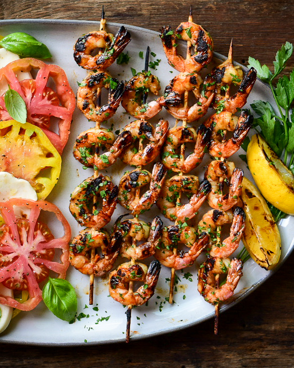 An image of four ridiculously good grilled shrimp on a plate with grilled lemons, parsley and an heirloom tomato salad.