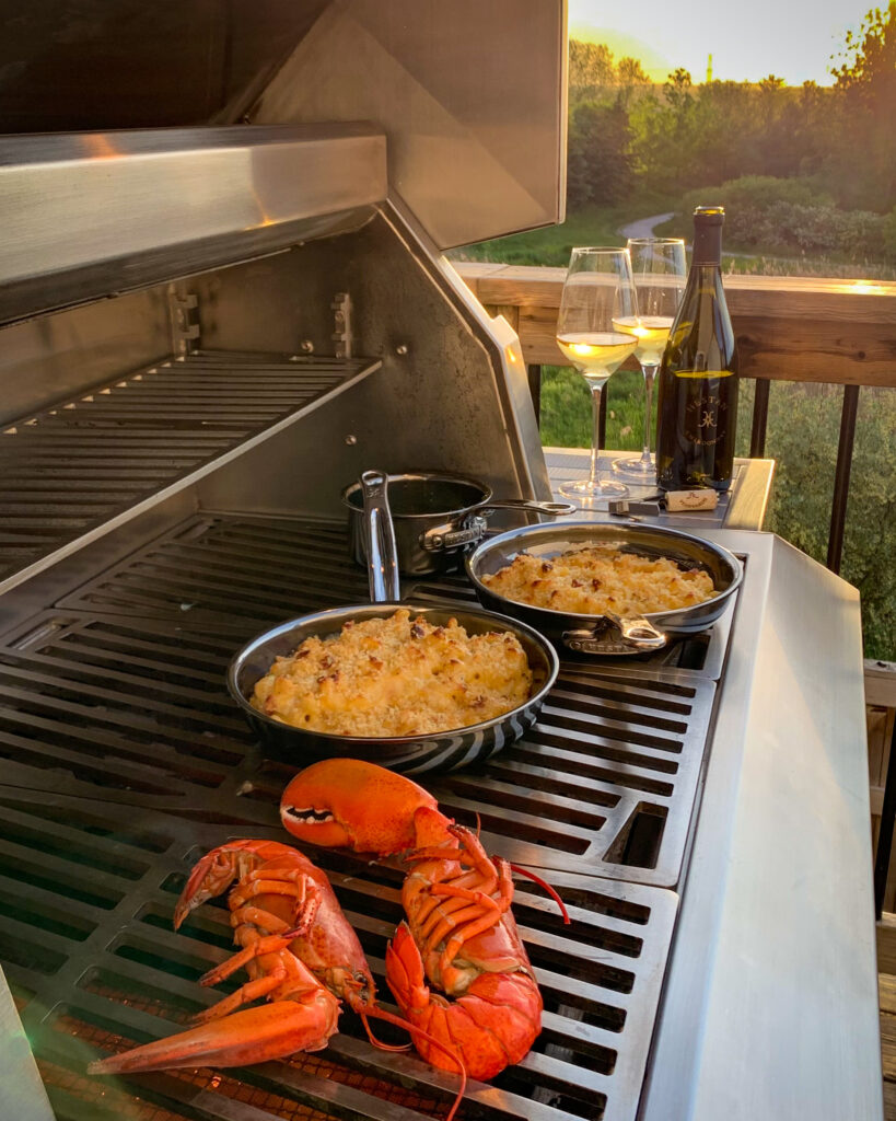 An evening photo of grilled lobster mac and cheese being made. There are two skillets each filled with mac and cheese, the half lobsters are directly on the grill. There is a sunset and a bottle of wine with two glasses filled.