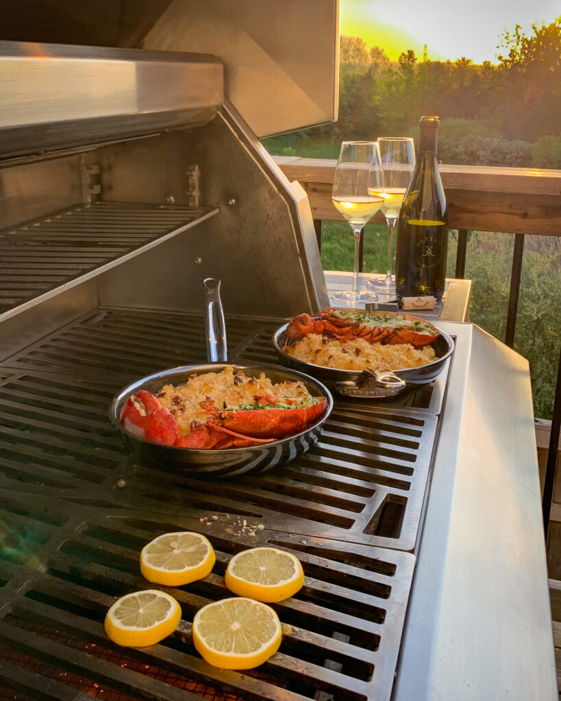 An evening photo of grilled lobster mac and cheese being made. There are two skillets each filled with mac and cheese plus a half lobster. There is a sunset and a bottle of wine with two glasses filled.