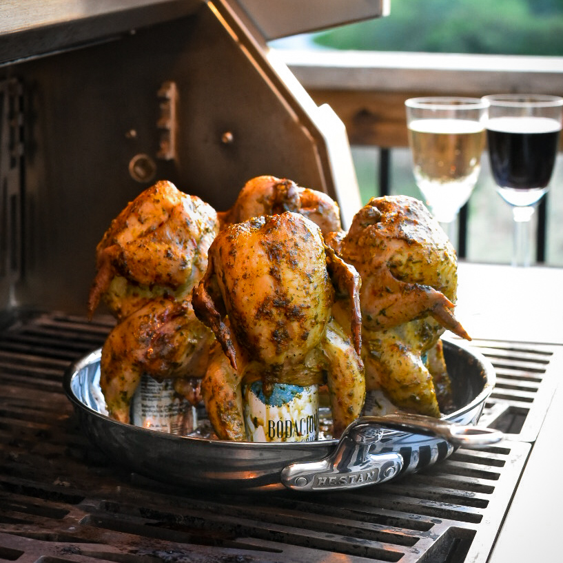 Four wine can Cornish hens are placed on a skillet on a grill. Two wine glasses (one white, one red) are in the background.