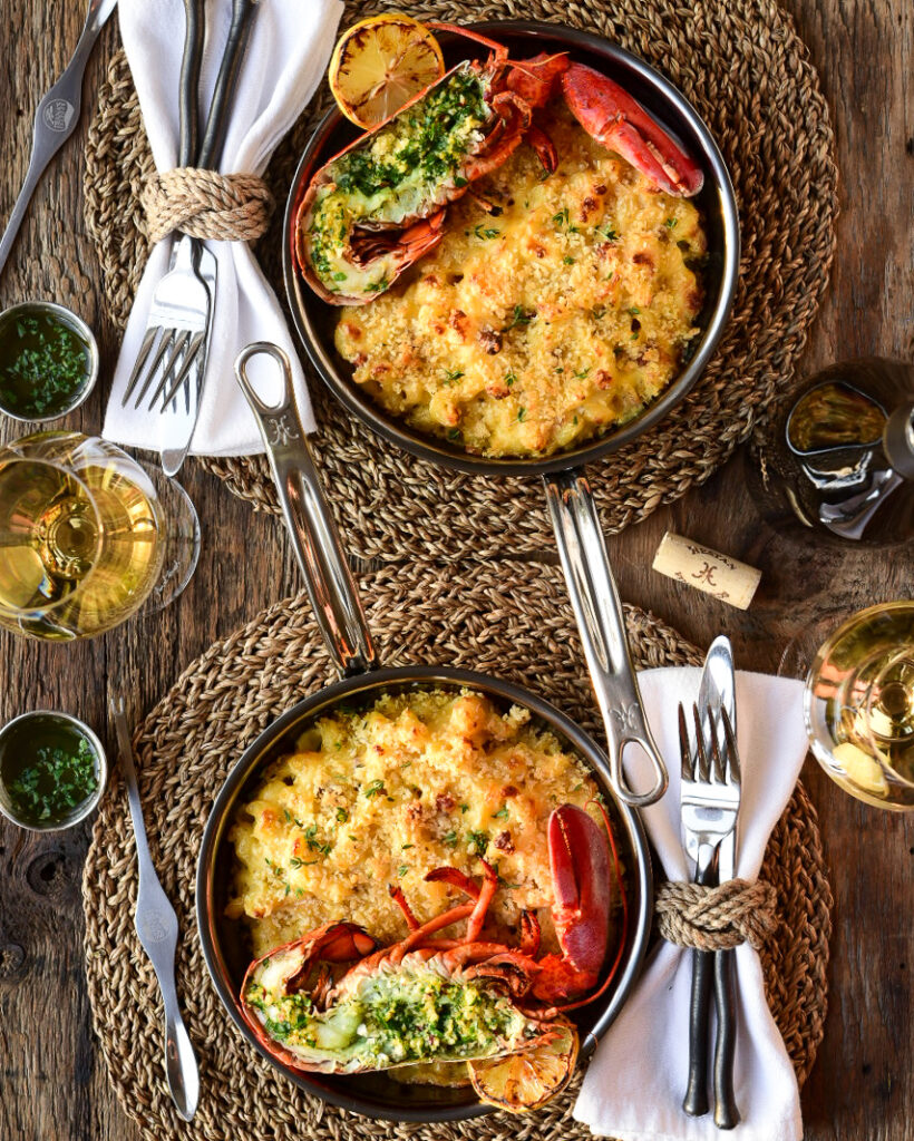 A top down image of two place settings on wicker placemats. Each setting has a skillet of grilled lobster mac & cheese, napkins, cutlery, wine glasses and bottle.