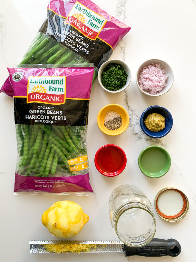 Ingredients for Earthbound Green Beans with Lemon, Dill, Dijon Dressing are portioned out in little colourful dishes beside two packages of beans.