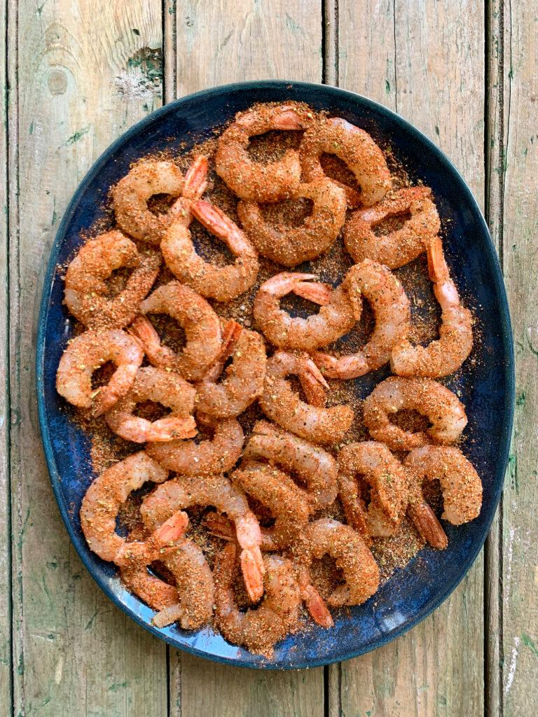 Seasoned raw shrimp on a blue oval plate.