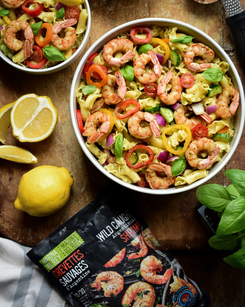 A top down image of a large and two smaller bowls of a Wild Argentinian Shrimp Pesto Pasta Salad on a wooden board. Basil, lemon's and Parmesan cheese.