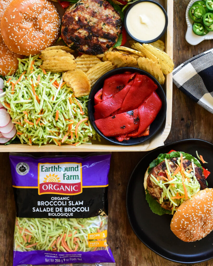 A top down image of a tray filled with burgers, roasted red peppers chips, sauce and Earthbound Organic Broccoli Slaw with Cider Dressing.