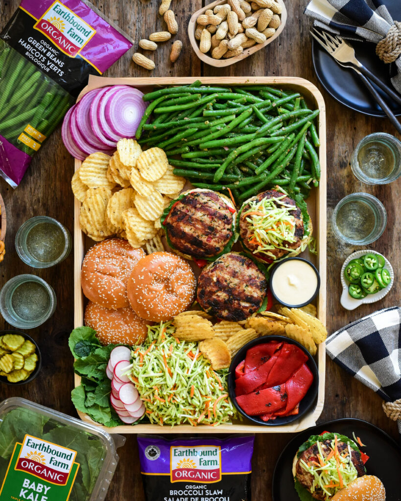 A tray of open-faced turkey kale & feta burgers, buns green beans, sliced red onions, chips, dip, broccoli slaw and roasted red peppers. Packages of baby kale, broccoli slaw and green beans surround this tray.