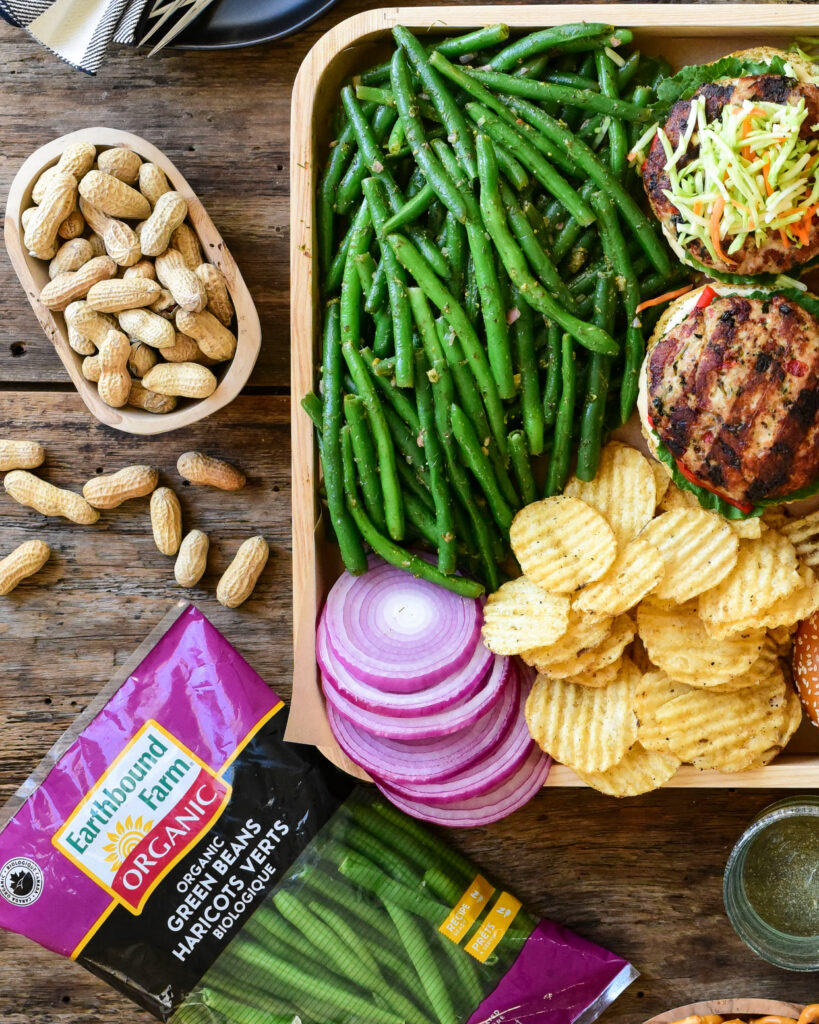 A top down image of a tray filled with Earthbound Green Beans with Lemon, Dill, Dijon Dressing with turkey burgers, ripple chips, sliced red onions. Outside of the tray is the package of Green Beans and a bowl of peanuts.