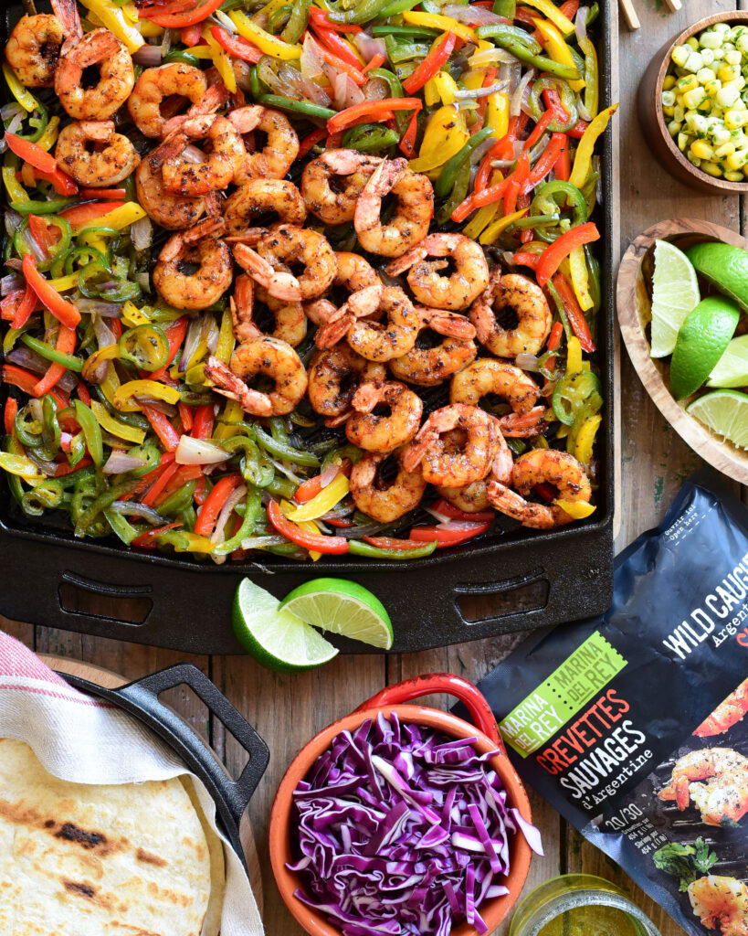 A top down image of a cast iron griddle with grilled tri coloured peppers, onions and shrimp. Surrounding this griddle are the fixings for sizzling steak fajitas and a bag of frozen shrimp.