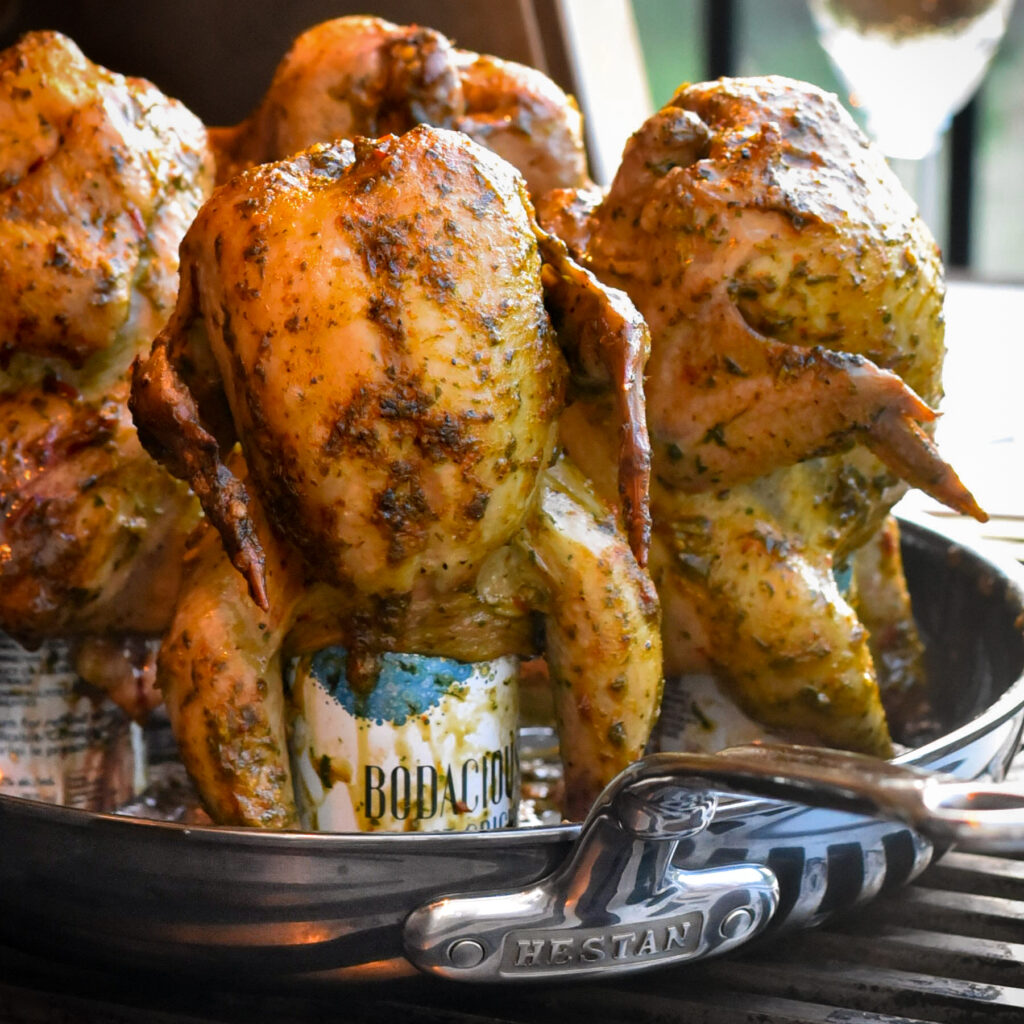 A close up of wine can cornish hens are placed on a skillet on a grill. The skin is crispy, golden brown.