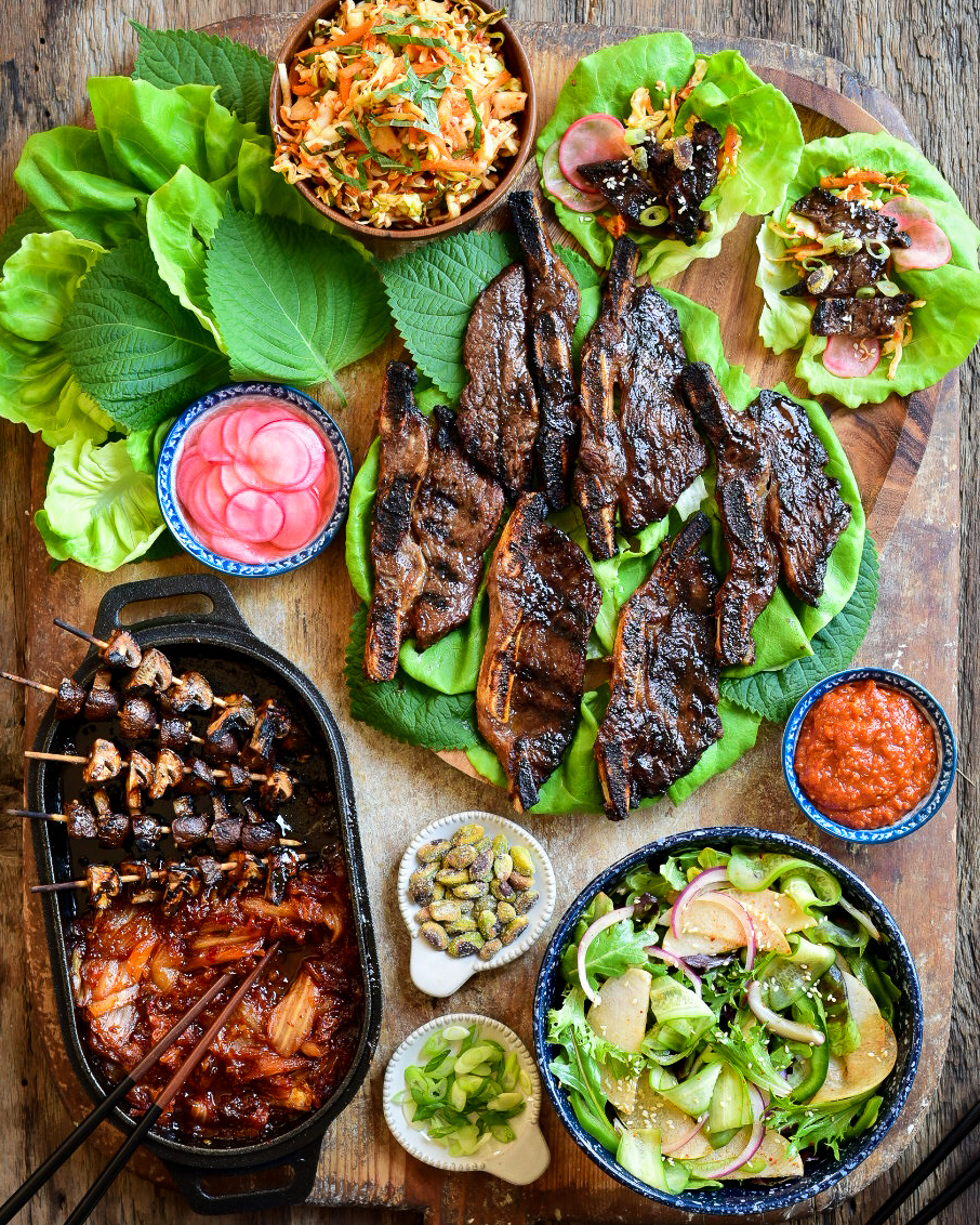 A top down image of barbequed Korean-style barbecue beef short ribs on lettuce and two dressed lettuce wraps on a large wooden board. Additional lettuce, radishes, sauce, pistachios, chopped green onion, a salad and a cast-iron dish with mushroom skewers and kimchi surrounding the beef.