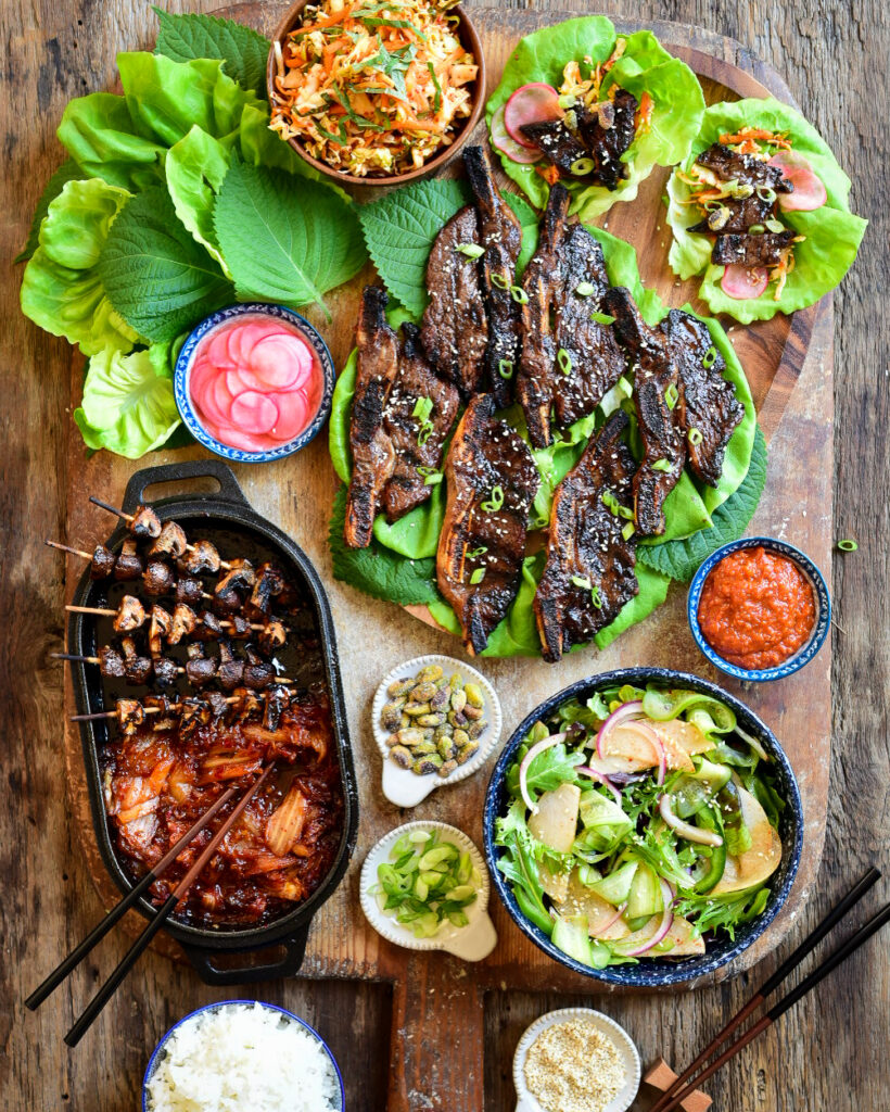 A top down image of barbequed Korean beef short ribs on lettuce and two dressed lettuce wraps on a large wooden board. Additional lettuce, radishes, sauce, pistachios, chopped green onion, a Korean Green Salad, rice and a cast-iron dish with mushroom skewers and kimchi surrounding the beef.