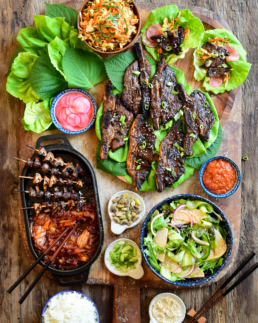 A top down image of barbequed Korean-style barbecue beef short ribs on lettuce and two dressed lettuce wraps on a large wooden board. Additional lettuce, radishes, sauce, pistachios, chopped green onion, a salad, rice and a cast-iron dish with mushroom skewers and kimchi surrounding the beef.