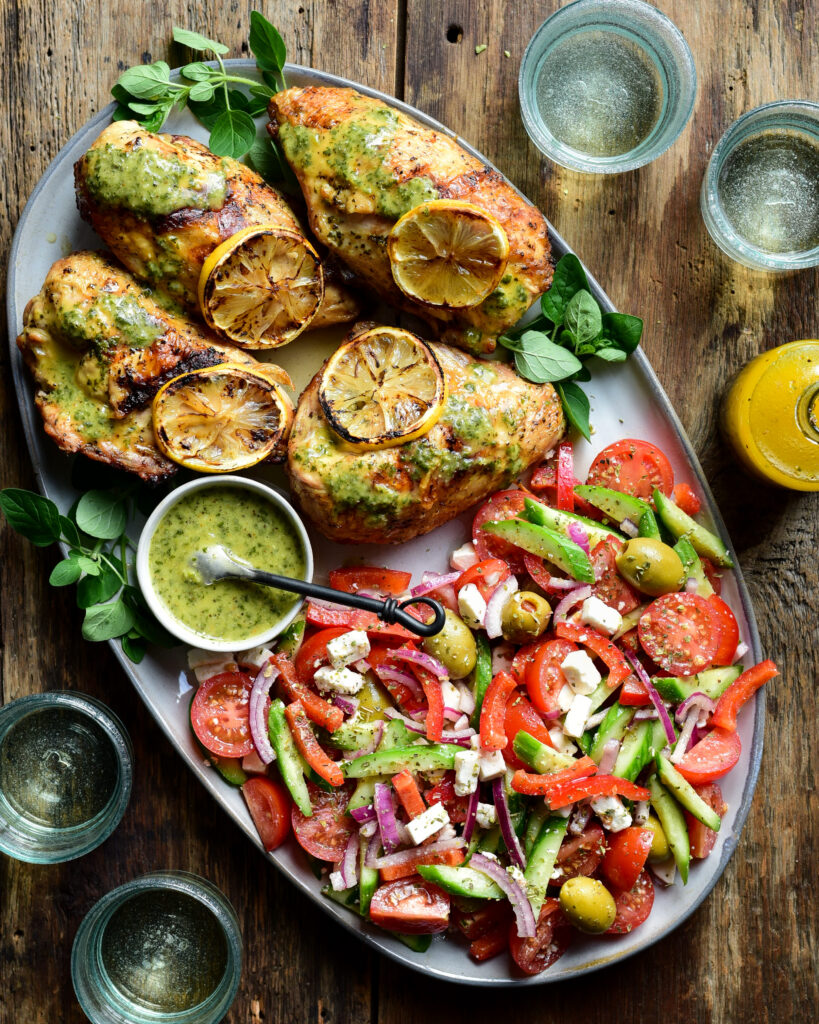 An oval platter with four grilled lemon-oregano chicken breasts, a bowl of sauce and a village salad. Four wine glasses surround this platter.