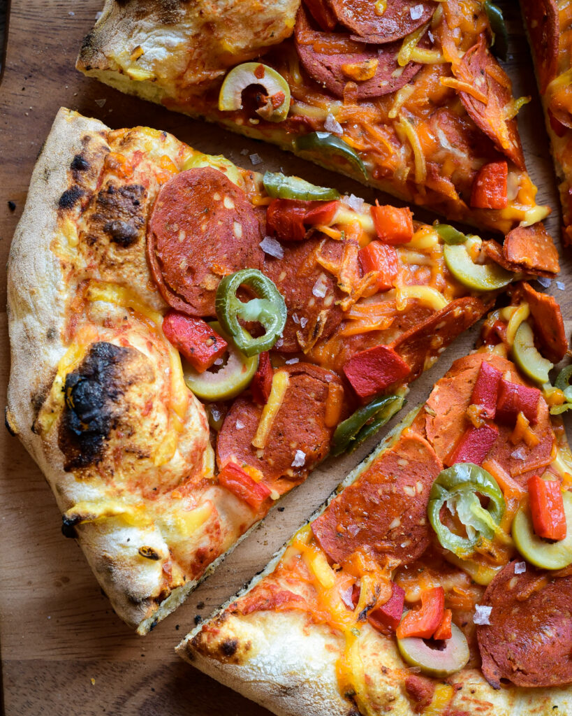 A close up image of a plant-based pepperoni pizza slices,