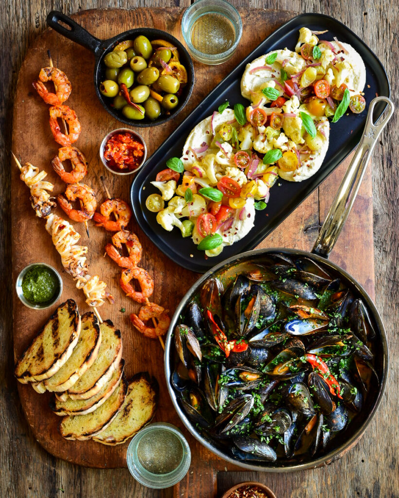 A top down image of Red Thai Curry Mussels in a skillet. A dish of hummus and veggies, shrimp & calamari skewers, toast, olives, hot chilli sauce and two glasses of wine surround the skillet