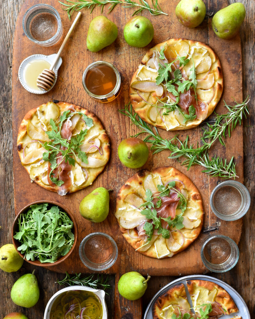 This is a top down image of three Ontario Pear & Prosciutto Naan-Pizzas with a pot of honey, rosemary sprigs, Bartlett pairs and glassed of wine on a wooden cutting board.